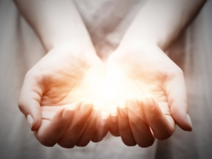The light in young woman hands in cupped shape. Concepts of shar